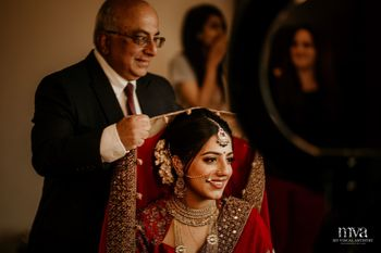 Bride getting ready with father placing dupatta on her head