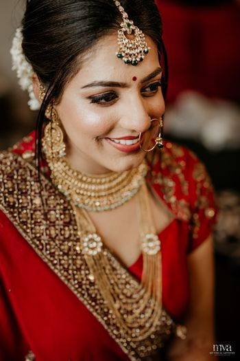 Simple bridal look in red lehenga and layered jewellery