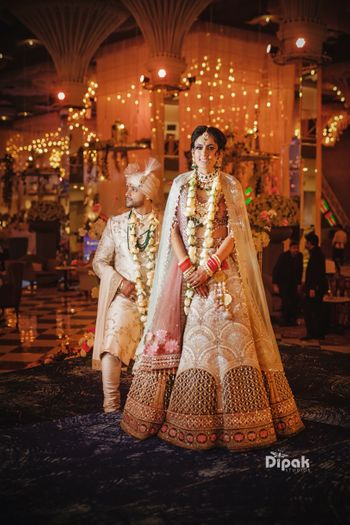 Photo of Bride and groom shot with pastel jaimala and unique lehenga