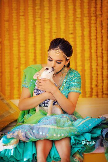 Bride in green mehendi lehenga kissing her dog