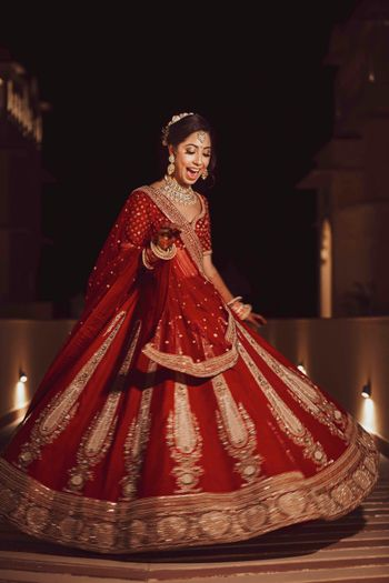 Bride twirling in red and gold simple lehenga