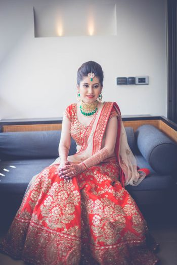Photo of Red bridal lehenga with emerald jewellery