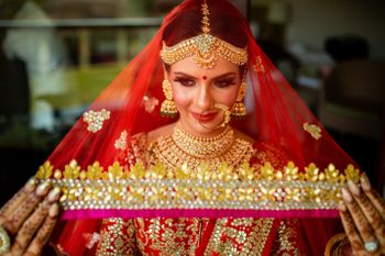 Bride holding her red and gold dupatta as a veil