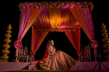 Bride in red posing against the mandap