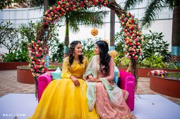 Bride with sister on arch bridal seat on mehendi