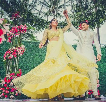 Groom and bride twirl shot idea with yellow lehenga