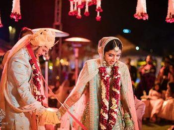 Offbeat bride during phera shot with maroon jaimala