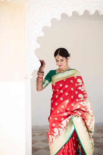 Contrasting green blouse with red benarasi saree
