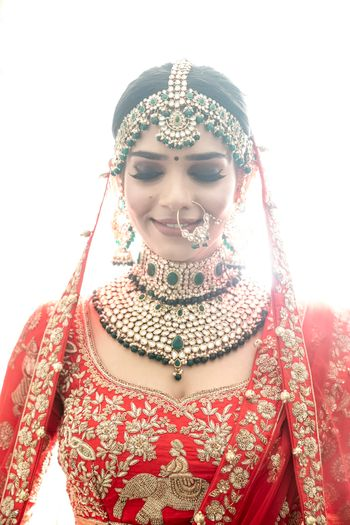 Contrasting green jewellery with red lehenga for north indian bride