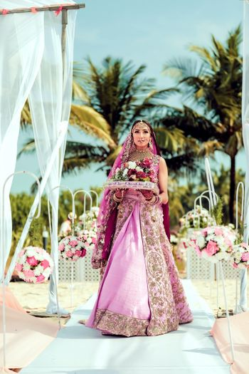 Bridal entry in light pink lehenga holding bouquet