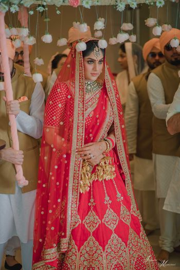 Bride entering with phoolon ki chadar with hanging roses