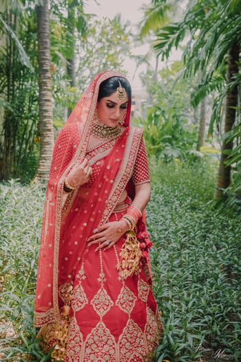 Coy bridal portrait in a red bridal lehenga