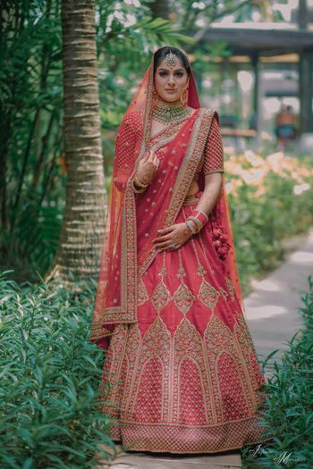 Bride in red with embroidered bridal lehenga