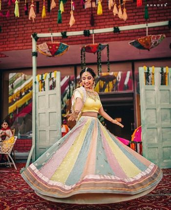 A bride in a pastel patchwork lehenga twirling on her mehendi day