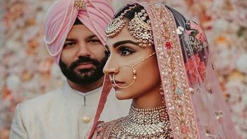 Photo of Sikh couple in light pink outfits and unique jewellery