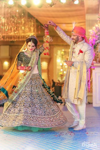 Couple Dancing Shot in Black Lehenga and Sherwani