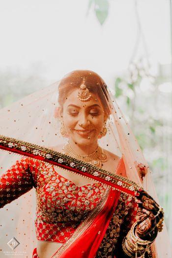 Bridal portrait holding her dupatta as veil