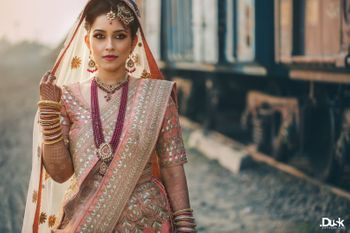 A bride in a pink lehenga and contrasting maroon colored jewels