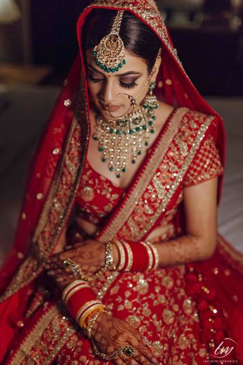 Bridal portrait with red lehenga and green jewellery