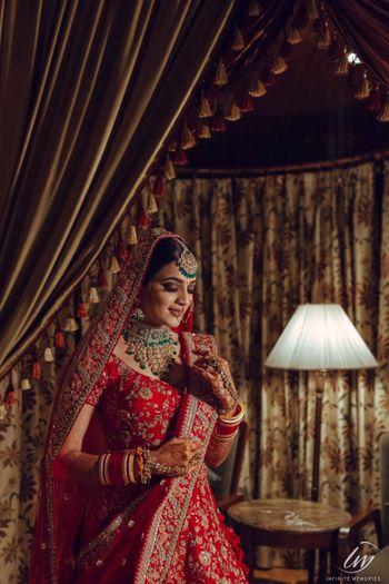 Bridal portrait in room in red lehenga and green jewellery