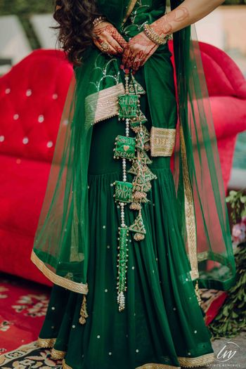 Personalised bridal lehenga in dark green with latkans