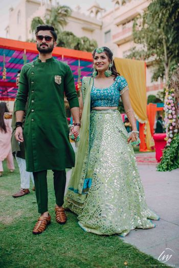 Bride and groom on mehendi in contrasting outfits of same shade