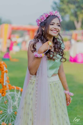 Bride in light green lehenga and pink floral jewellery on mehendi