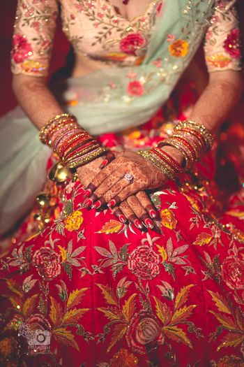 Bridal hands on floral embroidered lehenga