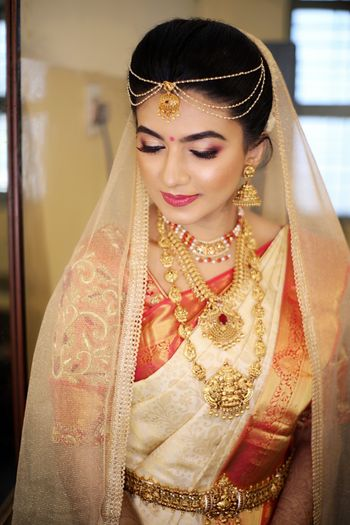 Beautiful bridal shot of a South Indian Bride with a dupatta as a veil.