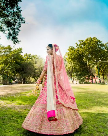 A happy shot of a twirling bride on her wedding day, dressed up in a beautiful pink lehenga with golden embroidery and pink chooda.