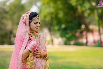 A beautiful bride dolled up in a light pink lehenga on her wedding.