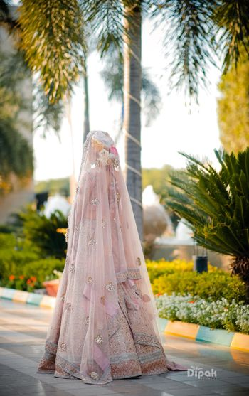 Bridal back shot in pastel lehenga and bun