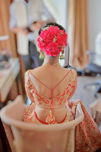 A bride wearing oversized flowers with baby breath in her bridal bun.
