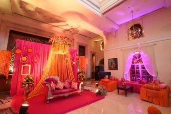 Photo of Mehendi sangeet stage decor with pink backdrop and marigolds