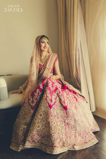 Photo of Beautiful Pink and gold bridal lehenga with light peach dupatta