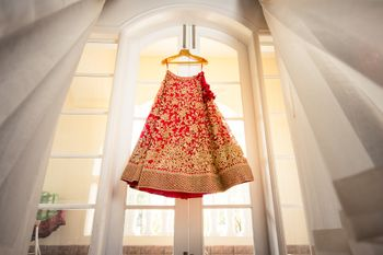 Photo of Red and gold lehenga on hanger