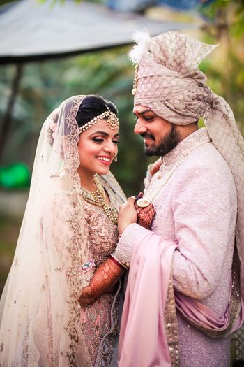 A romantic couple holding on each other beautifully dressed in pink outfits on their wedding.