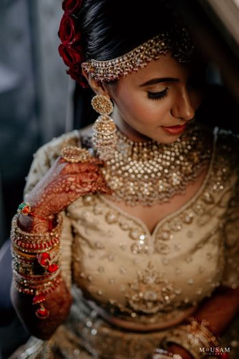 Photo of A bride in a gold lehenga and stunning jewelry on her wedding day