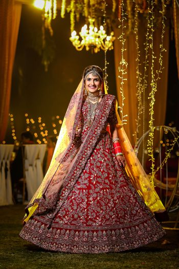 A pretty bride twirling in her beautiful red lehenga.