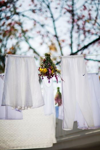 Super creative DIY decor with white clothes on a clothesline and floral bunches interspersed