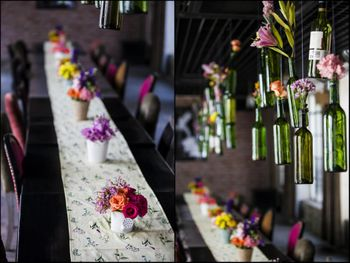 Photo of bottles with flowers hanging from ceiling over table