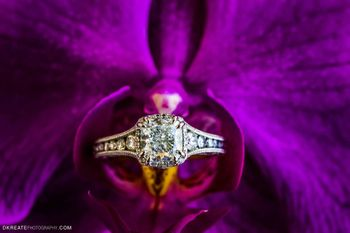 Photo of engagement ring on a purple flower