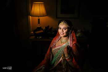 Bride in red and green lehenga for her wedding