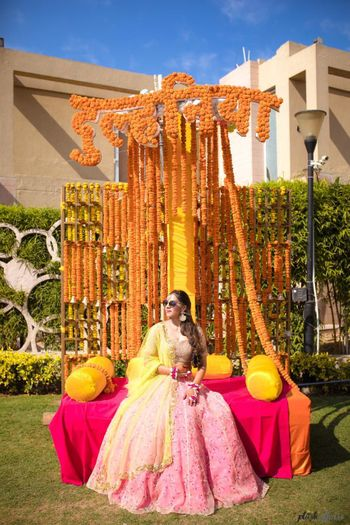 A bride in a light pink lehenga for her mehndi ceremony