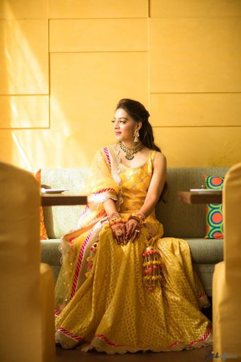 A bride in a yellow outfit and pompom kaleere for her mehndi
