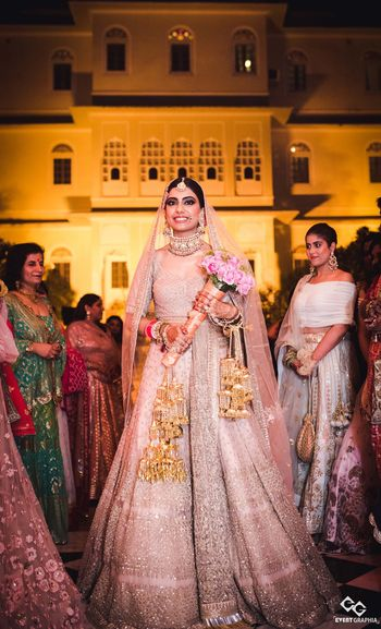 Photo of Bride holding bouquet wearing light pink lehenga