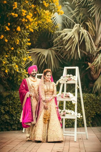 Coordinated bride and groom wearing pink and gold
