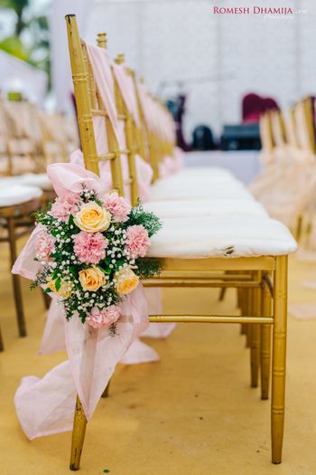 Neat, and pretty floral decoration pn chairs at a wedding