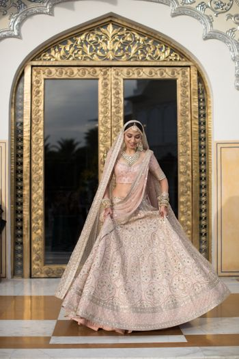 A stunning bride entering the room flaunting her fabulous lehenga.