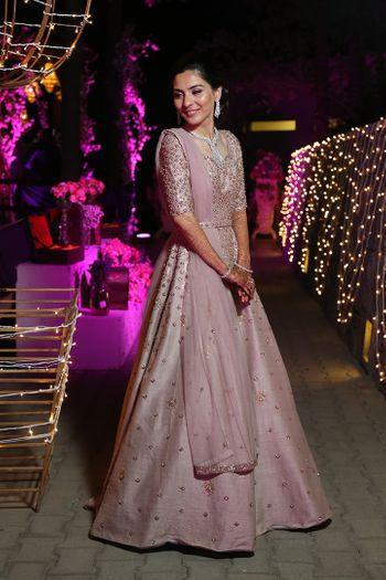A happy bride in a pastel anarkali on her reception.